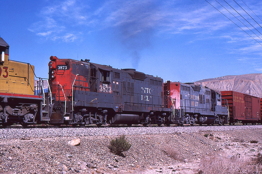 "SSW 3873 serves as a head-end helper on a westbound manifest train on the east side of Beaumont Hill in October of 1987. Note the ""5 CAB"" stencil above the number referring to its ability to accommodate a 5 man crew (part of the elimination of cabooses). Photo by John L. Shine"